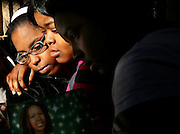 "The family of Antwanette Smith, 17, who  was accidentally shot , gather outside her East Orange home.  Smith's cousin Jasmine Barber, 15, Smith's best friend Rajanae ""Nea-Nea"" Williams, 16, and cousin Latesha Jones, 11, RIGHT,   comfort each other as they look at a photo of her."