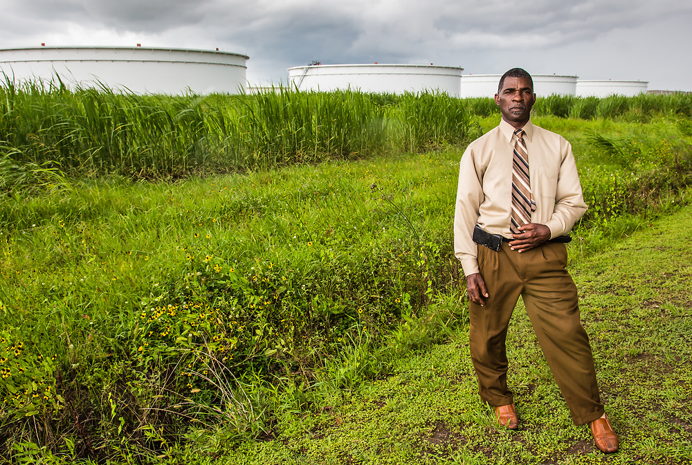 Pastor Harry Joseph near oil storage tanks in St. James, close to the Mount Triumph Baptist Church