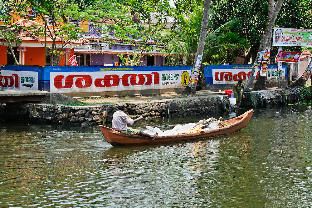 A man transports goods by boat on the Kerala Backwaters