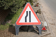 Red triangular sign warning of road narrowing ahead, UK