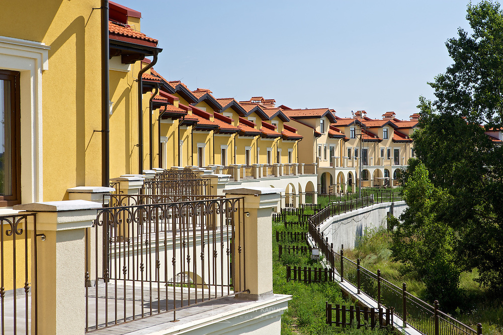Daylight exterior shot of residential townhouses buildings on the territory of real estate development project Italian Village in Kyiv, Ukraine. Shows details of balconies with terraces on the foreground.