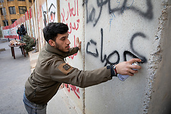 © Licensed to London News Pictures. 27/01/2020. Beirut, Lebanon. A man sprays graffiti onto security barricades around the government buildings in Downtown Beirut, as the government votes on the 2020 budget. Anti government demonstrators have been campaigning against government corruption and economic crisis for 103 days in Lebanon. Photo credit : Tom Nicholson/LNP