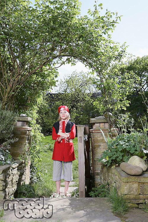 Portrait of young boy (7-9) wearing pirate costume standing in garden