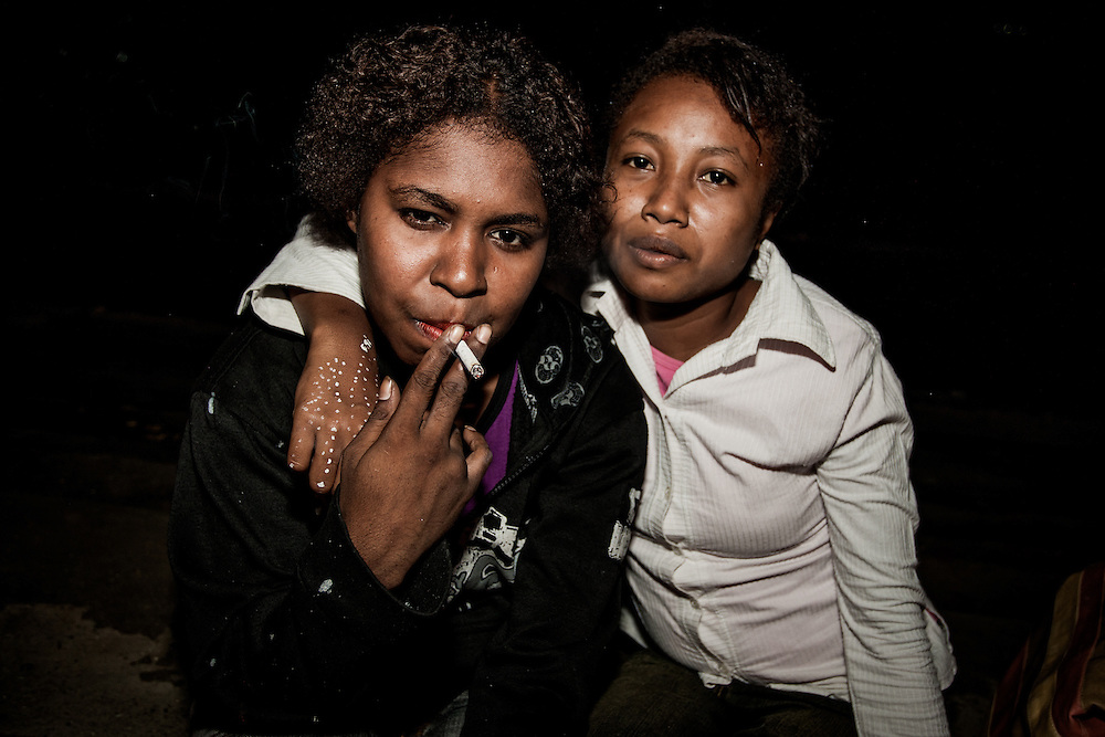 Papuan street prostitutes, B. (25) and N. (16) share a cigarette as they wait for potential clients.<br /> <br /> For many young Papuan women in urban and developing areas, poverty and economic pressures have forced the exchange of sex for goods, cash, or food as an accepted mean for survival.  Unlike non-Papuan brothel workers, Papuan sex workers often seek clients in public venues and have sex outside, by the side of the road, or in urban dwellings.  Operating outside formal establishments, the exact number of Papuan sex workers are unknown but are estimated to be at least double the number of non-Papuans.  Despite their high numbers, intervention programs targeting Papuan sex workers have not been a priority and most of them rarely have access to information, preventive services and support for HIV/AIDS and STDs.  With limited access to information and support, Papuan sex workers are less informed, have lower rates of condom usage (5% compared to non-Papuans with a 70% rate of condom usage), and are more likely to get infected with STDs and HIV than their counterparts in regulated brothels.