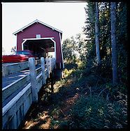 The Shimanek Bridge in Scio, Oregon. Red paint, portal design and louvered windows are features similar to the former span, which was built in 1927, and found on no other bridge in Linn County. Rods in the truss are grouped into a series of four instead of the usual three at each compression joint. The bridge shares the white painted interior of other Linn County bridges.
