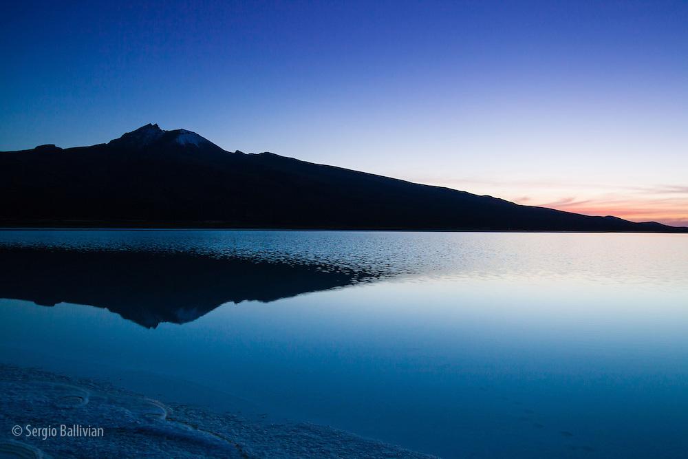 Subtle light slowly emerges during sunrise in Bolivia's flooded Salar de Uyuni during the rainy season.