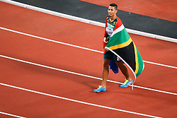 London, August 10 2017 . Wayde van Niekerk, South Africa, is draped in his country's flag after claiming silver in the men's 200m final on day seven of the IAAF London 2017 world Championships at the London Stadium. © Paul Davey.
