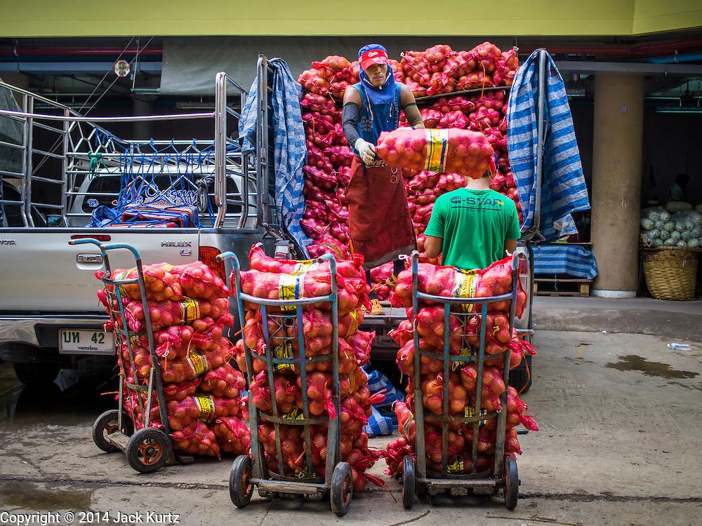 21 OCTOBER 2014 - BANGKOK, THAILAND:  Laborers unload a truck load of onions in the Pak Khlong Talat market on the Chao Phraya River in Bangkok.   PHOTO BY JACK KURTZ