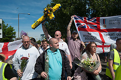 © London News Pictures. 26/05/2013. Woolwich, UK. Members of the EDL (English Defence LEague) and members of the public march past the scene where Drummer Lee Rigby was murdered by two men in Woolwich town centre in what is being described as a terrorist attack. Photo credit: Ben Cawthra/LNP