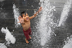 © Licensed to London News Pictures. 24/07/2018. London, UK. Aaron, aged 5, cools off in the water feature in London Bridge. [Permission to photograph verbally granted by parents]. Temperatures in the South East of the UK are reaching over 30 degrees celsius today, following the hottest day of the year yesterday. Photo credit : Tom Nicholson/LNP