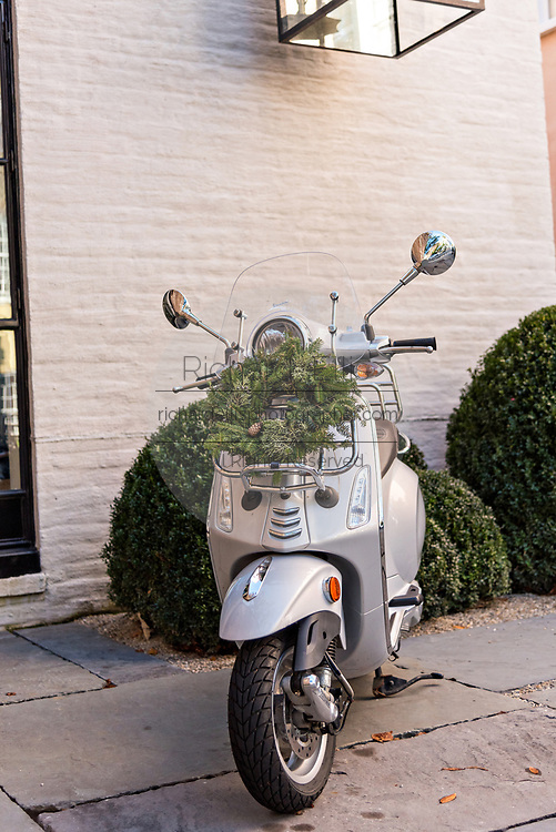 A Christmas wreath hangs from a Vespa scooter parked in front of a historic home along Church Street in Charleston, SC.