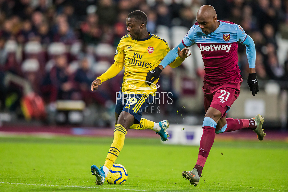 Nicolas Pepe (Arsenal) with control of the ball and Michail Antonio (West Ham) alongside during the Premier League match between West Ham United and Arsenal at the London Stadium, London, England on 9 December 2019.
