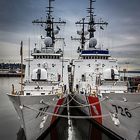 Two Coast Guard Cutters tied up together at their base in Seattle where they are docked behind a Coast Guard Heavy Icebreaker.
