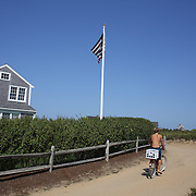A beach goer leaves Cisco Beach, Nantucket, on his bike. Nantucket Island, Massachusetts, USA. Photo Tim Clayton