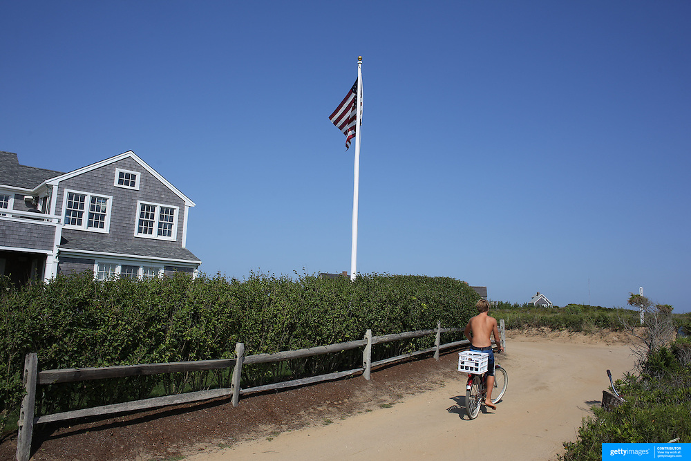A beach goer leaves Cisco Beach, Nantucket, on his bike. Nantucket Island, Massachusetts, USA. Photo Tim Clayton