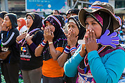 "15 JANUARY 2014 - BANGKOK, THAILAND: Thai Muslim women pray during morning prayers at the main stage for Shutdown Bangkok. Wednesday morning prayers were led by Buddhist monks, Muslim imams and a Catholic priest. Tens of thousands of Thai anti-government protestors continued to block the streets of Bangkok Wednesday to shut down the Thai capitol. The protest, ""Shutdown Bangkok,"" is expected to last at least a week. Shutdown Bangkok is organized by People's Democratic Reform Committee (PRDC). It's a continuation of protests that started in early November. There have been shootings almost every night at different protests sites around Bangkok. The malls in Bangkok are still open but many other businesses are closed and mass transit is swamped with both protestors and people who had to use mass transit because the roads were blocked.    PHOTO BY JACK KURTZ"