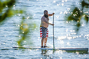 Ithaca, New York - July 05, 2014: Matt Fouse paddle boarding during Fourth of July Weekend in Ithaca, NY at Monica and Derick's lake house.<br />
