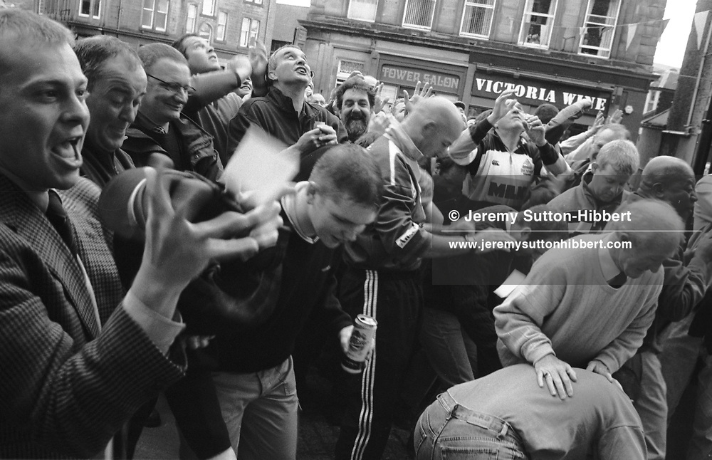 Men fighting to catch sachets of snuff tobacco thrown from the window of Drumlanrig Tower at 6am, during Hawick Common Riding week.. Scotland..PIC©JEREMY SUTTON-HIBBERT 2000..