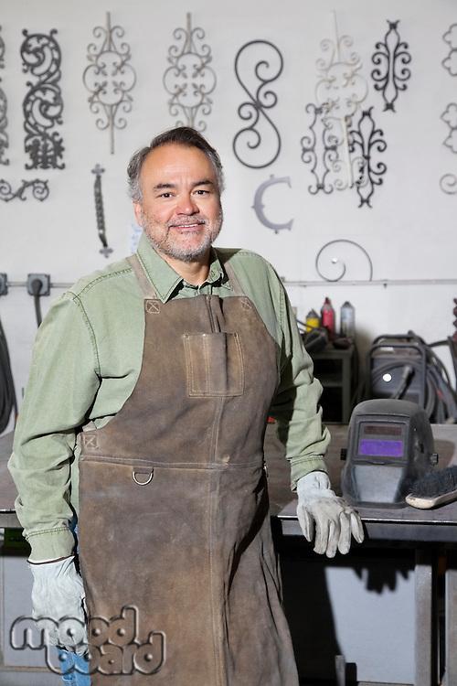 Portrait of a happy mature metalworker in workshop
