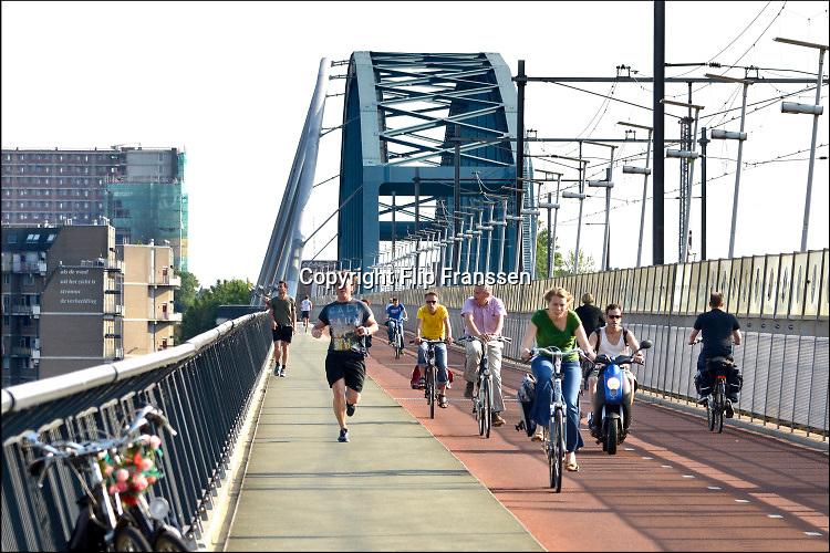 Nederland, Nijmegen, 8-7-2014 Fietsbrug, de snelbinder, die aan de spoorbrug is gehangen, en de verbinding vormt tussen de Waalsprong, nieuwe vinexwijken in oosterhout en Lent, en het centraal station. Hij is onderdeel van de snelfietsroute naar Arnhem. Foto: Flip Franssen