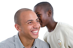 Young boy whispering into man's ear,
