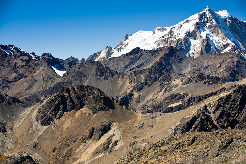 The rugged glacier-covered summit of Mt. Huayna Potosi (19,975') looms large and inaccessible in Bolivia's Cordillera Real of the Andes.