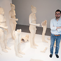 London, UK - 29 January 2014: artist Simon Fujiwara stands next to terracotta-dyed life sized plaster casts. His work Rebekkah, comprising 100 terracotta-dyed life sized plaster casts of a 16-year-old girl who took part in the 2011 London riots, goes on display at the Contemporary Art Society until 29 March.