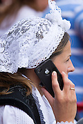 Woman in traditional costume using modern iPhone during fiesta at Villaviciosa in Asturias, Northern Spain