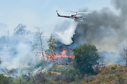 July 13, 2015 - Yorba Linda, CA, USA - <br /> <br /> water planes take to the sky to help put out fires<br /> <br /> A Cal-Fire helicopter drops water on a building as it burns at Irvine Lake. A vegetation fire that grew to burn more than 100 acres Monday morning, threatened some structures near Irvine Lake and caused officials to close down Santiago Canyon Road in unincorporated Orange County, California<br /> ©Exclusivepix Media