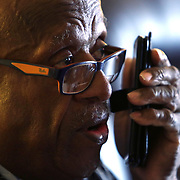 Mr. Johnson on the phone. John E. Johnson, who is not eligible for medicaid, receives services for 12 hours per week through Illinois' Community Care Program. Johnson worries his services will be cut if the state transition seniors like him to a new program. The state employs Reggie Griffin to help Johnson with daily chores so he is able to stay in his home, as opposed to going to an nursing home. <br /> Photography by Jose More