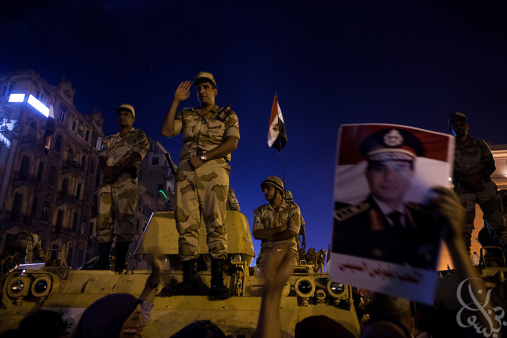 "Egyptian soldiers wave to the crowd as they stand in their positions to protect demonstrators during mass demonstrations called for by Gen. Abdel Fattah El Sissi, the head of Egypt's military, in the Tahrir Square area of downtown Cairo Egypt on Friday July 26, 2013. EL Sissi had asked Egyptians to take to the streets on Friday to show the world that he had a mandate to deal with ""violence and terrorism"", ahead of what many believe is a planned crackdown on the Muslim Brotherhood political group."