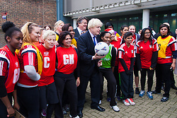 Ealing, London, December 9th 2014. Mayor of London Boris Johnson visits Ealing, Hammersmith and Fulham College accompanied by   Deputy Mayor for Policing and Crime Stephen Greenhlagh to launch a new initiative to increase black and ethnic minority applicants to the Met. PICTURED: Boris Johnson poses with netball players after a game with them.