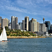 Sailing by Barangaroo Reserve in Sydney, Australia<br /> The CBD skyline attests to how Sydney is becoming a glass city. Fortunately, it is working hard to retain its historic lineage and natural beauty. This Millers Point headland in Sydney Harbour showed archeological evidence of Aboriginal people going back millenniums. In the 19th century, this land contained factories. After the industrial buildings were torn down, over 10,000 sandstone blocks were used and 75,000 trees were planted to reshape the 2.5 acres into Barangaroo Reserve. Since 2015, this landscaped park has become popular among walkers, joggers and cyclists