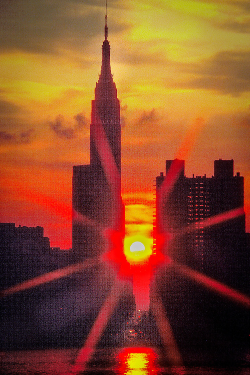 A fiery sun sets behind the Empire State Building and 34th Street in New York City's borough of Manhattan as seen from across the East River.