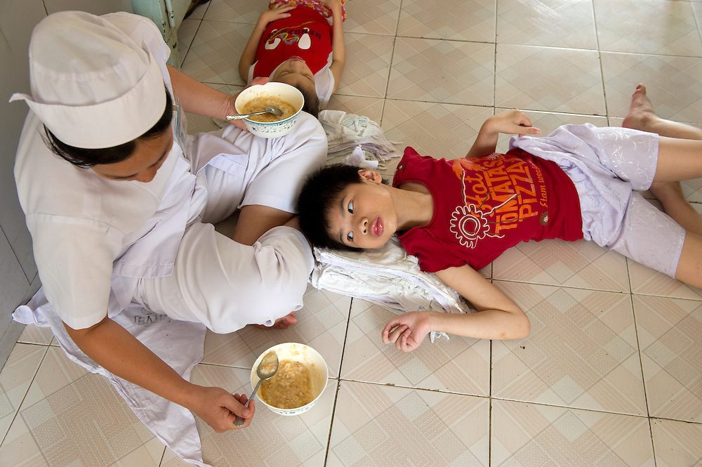 Nurse Tran Thi Mai Lien, feeding young patients at the Peace Village within the Tu Du (Freedom) Obstetrics and Gynaecology Hospital in Ho Chi Minh City, Vietnam
