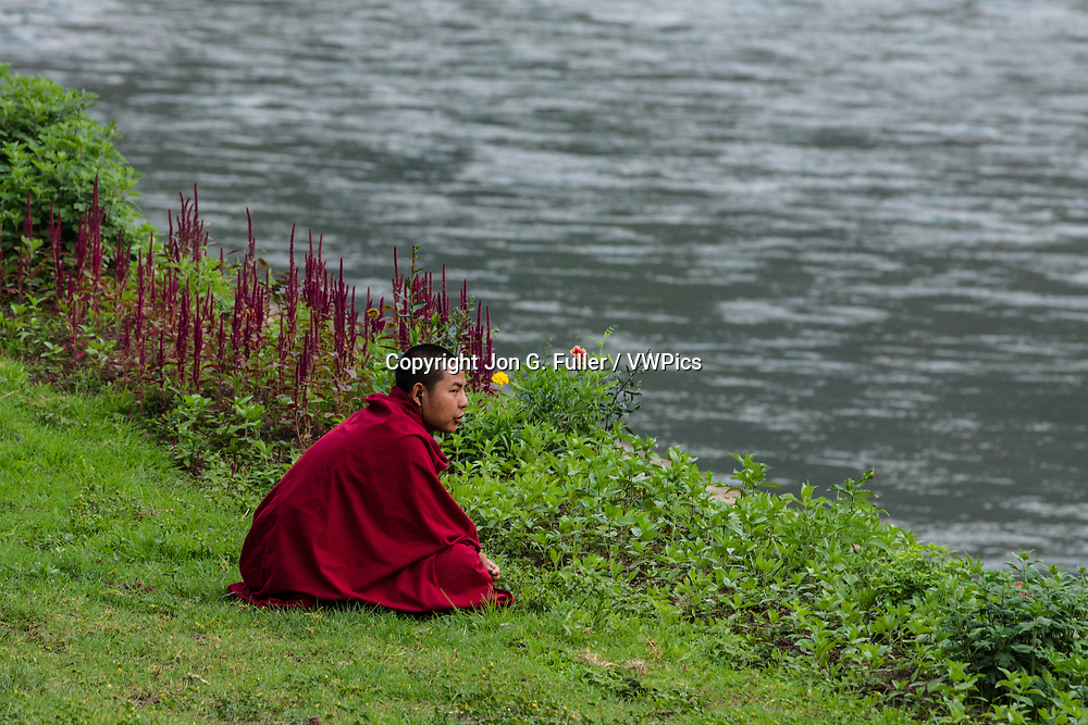 A young novice Buddhist monk sits in the grass and listens with his earbuds while sitting on the bank of the Mo Chhu River at the Punakha Dzong in Punakha, Bhutan.