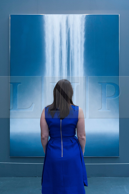 """© Licensed to London News Pictures. 19/05/2016. London, UK. A visitor looks at Hiroshi Senju's """"Waterfall"""".  Art16 opens at Olympia, in west London.  Now in its fourth edition, the fair brings together over 100 galleries from more than 30 countries showcasing a diverse cross-section of work by contemporary artists from around the world for buyers and art enthusiasts to visit. Photo credit : Stephen Chung/LNP"""