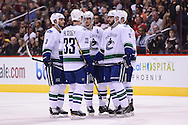 Nov 5, 2013; Glendale, AZ, USA; Vancouver Canucks forward Henrik Sedin (33) , defensemen Kevin Bieksa (3) , forward Daniel Sedin (22) and forward Ryan Kesler (17) talk on on the ice in the first period against the Phoenix Coyotes at Jobing.com Arena. The Coyotes defeated the Canucks 3-2 in an overtime shoot out. Mandatory Credit: Jennifer Stewart-USA TODAY Sports