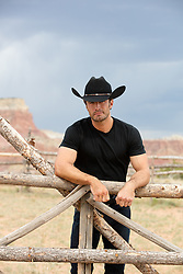 cowboy leaning on a ranch fence