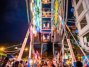 29 OCTOBER 2015 - YANGON, MYANMAR: A human powered Ferris Wheel during a street carnival in central Yangon. Electricity is scarce in Myanmar, especially in rural areas, and most traveling carnivals use human powered rides. Workers climb to the top of the Ferris Wheel and then pull it around getting it spinning. They do the same with Merry Go Rounds, but instead of climbing to the top they pull it around. The carnival coincided with the Thadingyut Festival, the Lighting Festival of Myanmar, which is held on the full moon day of the Burmese Lunar month of Thadingyut, October or November on the Gregorian calendar. The carnival featured food, rides and games.      PHOTO BY JACK KURTZ