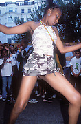 A young black girl dancing, wearing a short camouflage skirt, Notting Hill Carnival, London, UK 2004