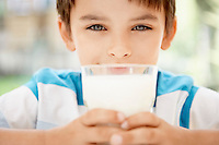 Young boy holding glass of milk portrait close up