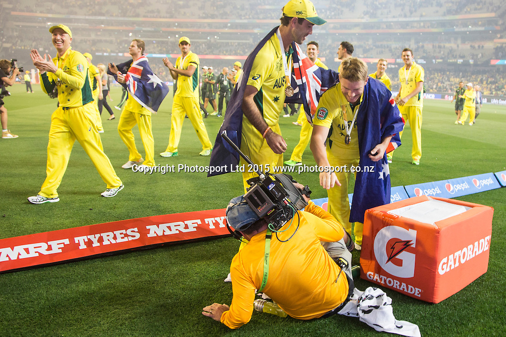 David Warner helps a camera man after he fell over a gatorade tub during the ICC Cricket World Cup Final match between Australia & New Zealand at the Melbourne Cricket Ground. Sunday 29th March 2015. Copyright Photo. Asanka Brendon Ratnayake / www.photosport.co.nz