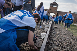 "12.04.2018, Konzentrationslager Auschwitz, Oswiecim, POL, ""March of the living"" am Weg aus dem ehemaligen deutschen Nazi-Todeslager Auschwitz I nach Auschwitz II - Birkenau, im Bild ein Teilnehmer steckt ein Schild in den Boden// participants during the 'March of the Living' from the former German Nazi death camp Auschwitz I to Auschwitz II - Birkenau at the concentration camp in Oswiecim, Poland on 2018/04/12. EXPA Pictures © 2018, PhotoCredit: EXPA/ Florian Schroetter"