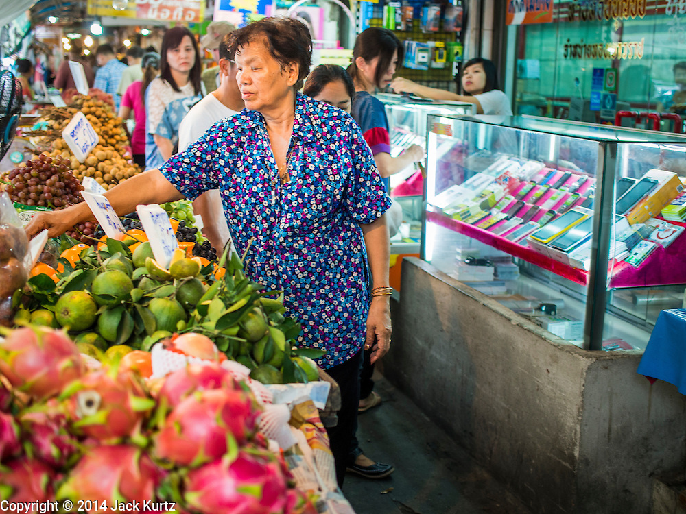 22 AUGUST 2014 - BANGKOK, THAILAND:      People shop and walk among the stalls set up on the sidewalks along Soi 77 (On Nut) off of Sukhmvit Road. The Thai military junta, formally called the National Council for Peace and Order (NCPO), has ordered street vendors off of the sidewalks in an effort to bring order to Bangkok's chaotic sidewalks. Vendors have complained that the new regulations are hurting them economically but largely complied with the military orders.      PHOTO BY JACK KURTZ