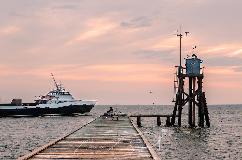 A boat passes a fisherman at the public fishing pier on the east end of Dauphin Island, Alabama near Fort Gaines. The popular spot is a haven for anglers, bird-watchers, and visitors watching the sun rise over Mobile Bay. (Photo by Carmen K. Sisson/Cloudybright)