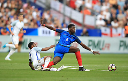 England's Raheem Sterling (left) and France's Paul Pogba battle for the ball during the International Friendly at the Stade de France, Paris.