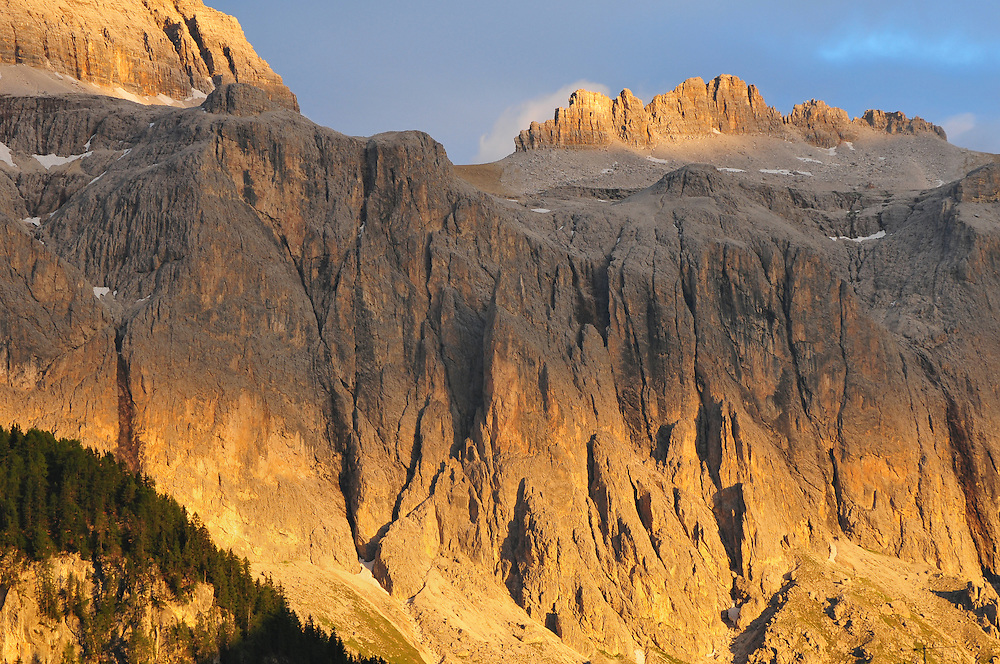 Light from the setting sun turns orange the rocky face of the Dolomites in Val Gardena, Italy<br />