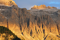 Light from the setting sun turns orange the rocky face of the Dolomites in Val Gardena, Italy<br /> (Val Gardena, Italy - July 2010)