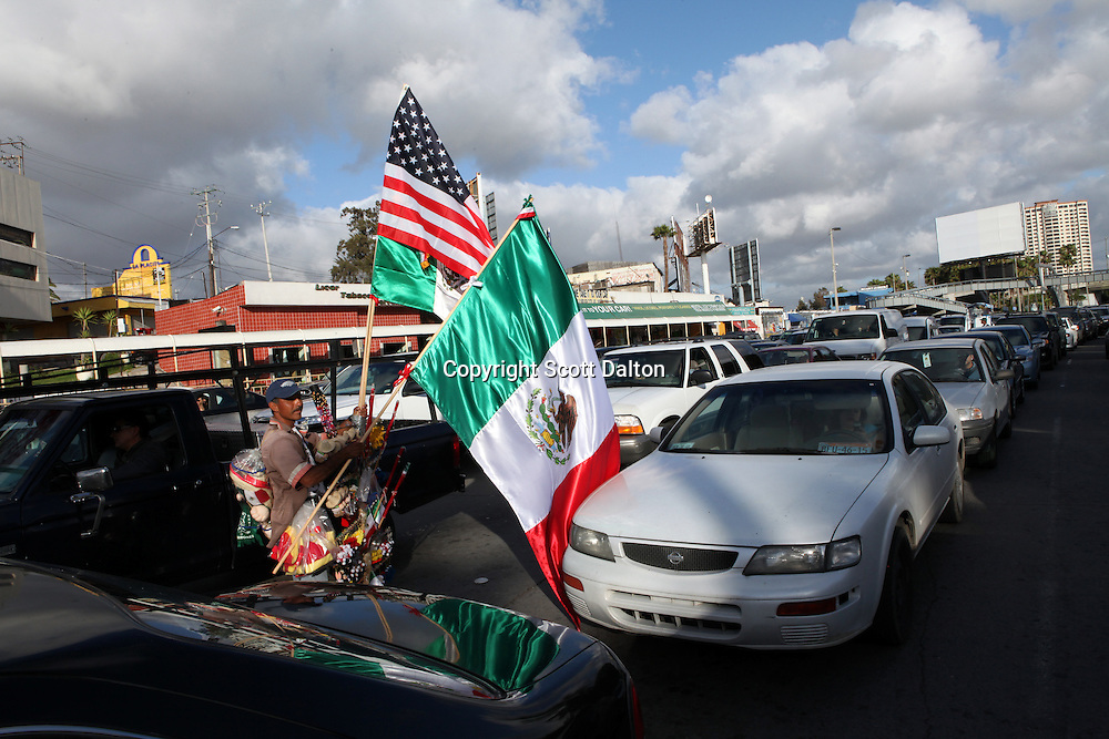 A man tries to sell US and Mexican flags to people in traffic in Tijuana, Mexico waiting to cross into the US at the San Ysidro port of entry on April 28, 2010. (Photo/Scott Dalton)